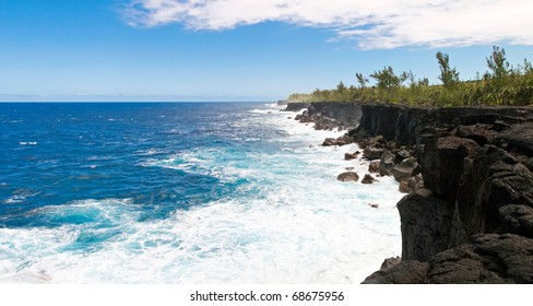 Waves breaking on volcanic cliffs of Reunion island with blue sky and cloudscape background.