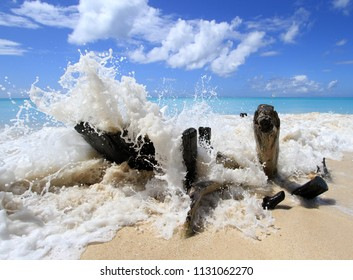 Waves breaking over driftwood on Ffryes Beach, Antigua