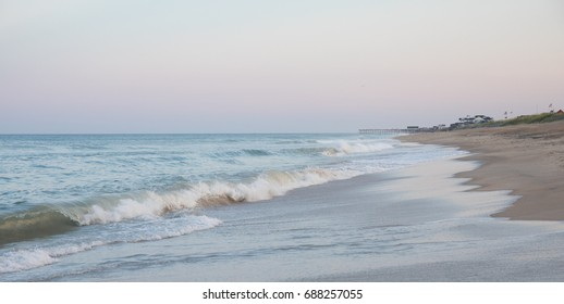 Waves coming ashore at the beach with a pier off in the distance.
