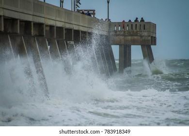 Waves crash against a concrete pier during a hurricane.