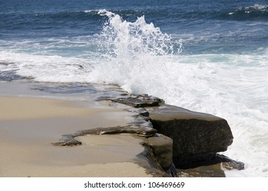 Waves crash against a rocky shore on the California coast.