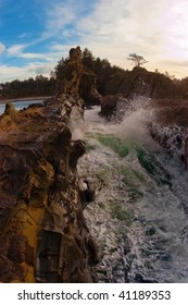 Waves crash against the sand rocks at Bastendorff Beach on the Oregon coast