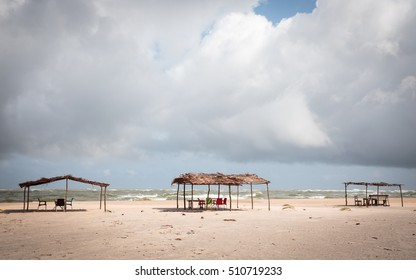 Waves crash against a sunbaked beach in Assinie, Cote d'Ivoire.  Local businesses try to rent shade huts to tourists but there are very few of these.
