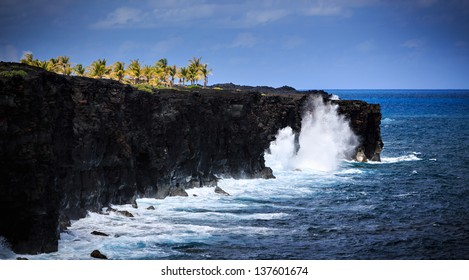 Waves crash along the black lava rock cliffs in the Hawaiian Volcanoes National Park.   This view is at the end of the Chain of Craters Road