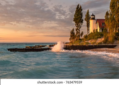 Waves crash along the Lake Michigan shore in front of Point Betsie Lighthouse, during sunset