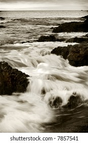 Waves crash in over a rocky coastline in sepia tone