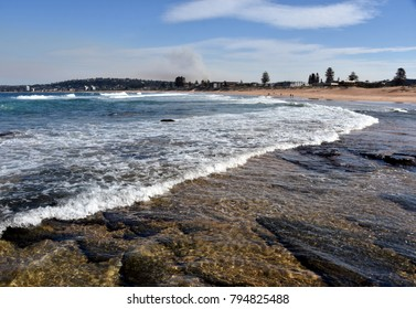 Waves crash and the water flows onto the rock shelf at Narrabeen beach (Sydney, Australia)