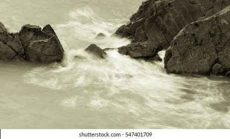 Waves Crashing Against Rocks in Devon A black and white long exposure photography