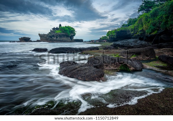 Waves crashing against rocks with the Tanah Lot temple in the background.
