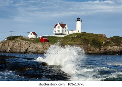"""Waves crashing at Cape Neddick (Nubble) lighthouse in York, Maine. The beacon sits a few hundred feet from the mainland on a small rocky island, known as a """"nubble""""."""