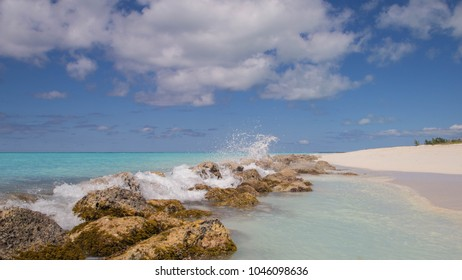 Waves crashing into rocks along the beach with beautiful turquoise waters and white sand. Taken in Turks and Caicos Islands.