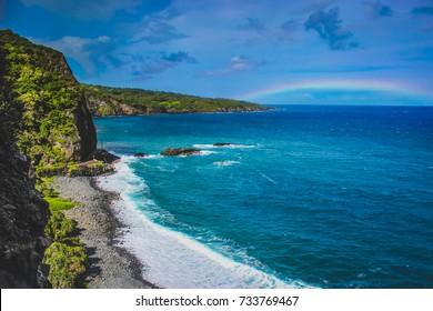 Waves crashing a Maui Beach with a rainbow in the distance on the Road To Hana, Maui, Hawaii