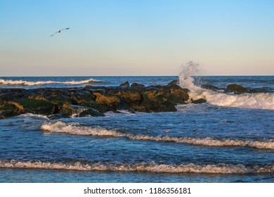 Waves crashing on jetty during very active surf along the coastline of Avon by the Sea in New Jersey.
