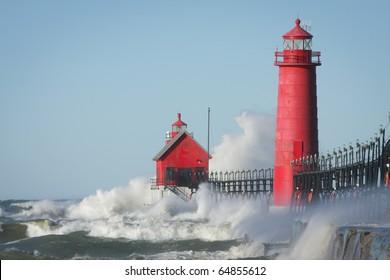 Waves crashing on lighthouse. Grand Haven lighthouse on Lake Michigan. Horizontal format.