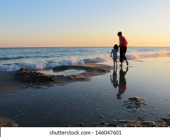 Waves crashing on the shore, with mother and child, Menorca