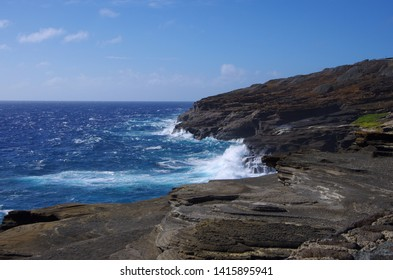 Waves crashing onto rock formations on a sunny day, at the Lanai Lookout in Oahu, Hawaii in the United States.
