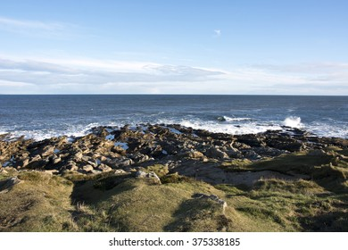 Waves crashing onto a rocky shoreline near Tarbet Ness lighthouse in the Highlands of Scotland.