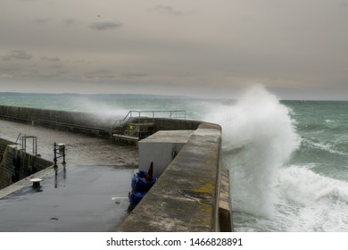 Waves crashing over mevagissey Harbour