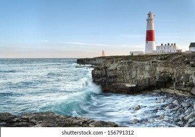 Waves crashing over rocks at Portland Bill lighthouse on the Jurassic Coast in Dorset