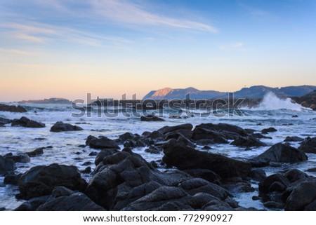 Waves Crashing Stones On Beach Sunshet Stock Photo (Edit Now