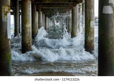 Waves crashing under pier