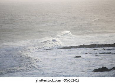 waves cresting and making land fall, spray coming of the top of the wave.