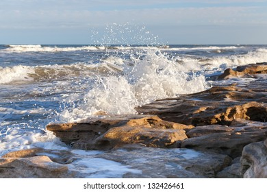 Waves crushing against a sandstone beach.