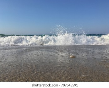 Waves crushing on a sandy beach in Ikaria, Greece