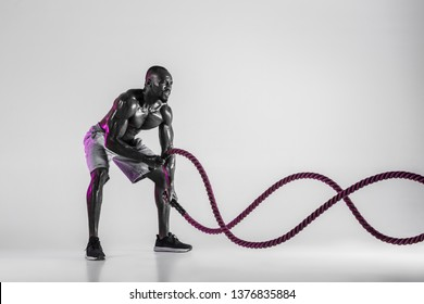Waves of force. Young african-american bodybuilder training over grey studio background. Muscular single male model in sportwear with battle rope. Concept of sport, bodybuilding, healthy lifestyle.