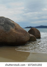 waves gently sweeping the strip of sand near rounded-shaped rocks leaving a mirror of water under a cloudy sky, De Cima beach, Pinheira, SC, Brazil