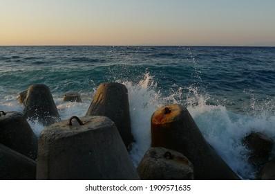 Waves hit the breakwaters in Aegean sea - Shutterstock ID 1909571635