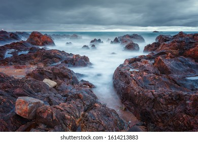Waves hitting on the rocks on the Portuguese coast. At dusk and due to the long exposure the water looks like a cloud floating on the rocks, Porto, Portugal