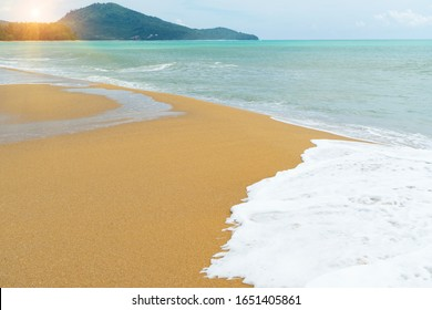 Waves and inshore currents then progressively shift sand to the beach with mountain and sunlight background.Summer holiday to visit the sea beach.