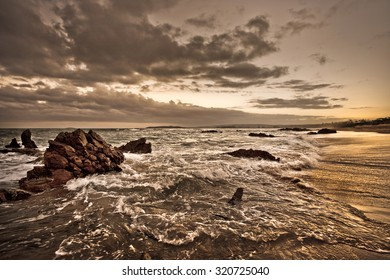 Waves moving over the rugged rocks and beautiful beach at sunset