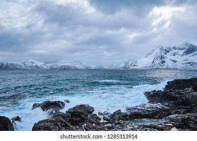 Waves of Norwegian sea crushing at rocky coast in fjord. Vikten, Lofoten islands, Norway