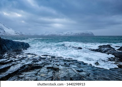 Waves of Norwegian sea crushing at rocky coast in fjord. Vikten, Lofoten islands, Norway