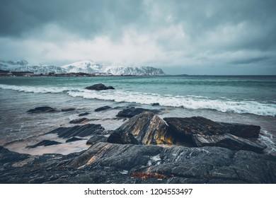 Waves of Norwegian sea on rocky beach of fjord. Ramberg beach, Lofoten islands, Norway
