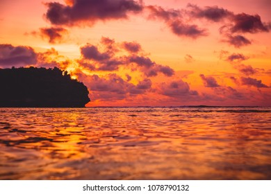 Waves in ocean and sunset with clouds. Ocean with sunset colors