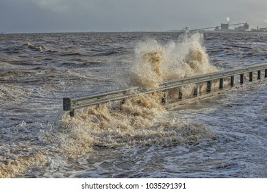Waves of ocean water splashing on a Dutch dike after heavy rains and storm in a coastal town in the Netherlands