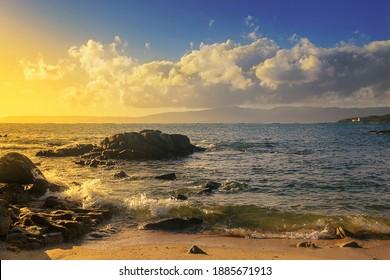 Waves on the coast of Arruda beach in Arousa island at golden sunset