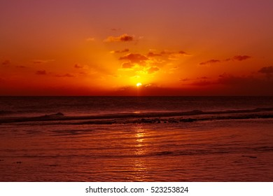 Waves on a red sunset in warm caribbean sea