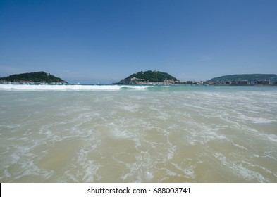 "Waves on a sandy beach of San Sebastian with ""La Perla"" island on the background"