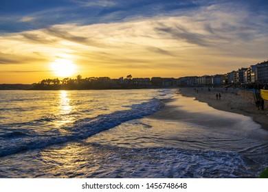 Waves on Silgar beach in Sanxenxo touristic city at golden sunset