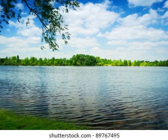 waves on water of lake and green trees on sky background