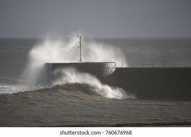 waves over wall crashing into wall