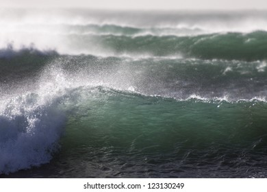 waves pour in/ a set of waves breaking, each one bigger than the previous