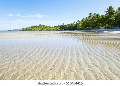 Waves ripple on the shallows of a wide remote tropical Brazilian island beach in Bahia, Nordeste Brazil