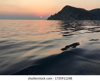 Waves ripple as the sun dips below water