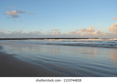 Waves are rolling onto a empty beach past a stone breakwater. The sky is blue, with clouds changing colour with the sunset. These colours are relfected in the water and wet sand.