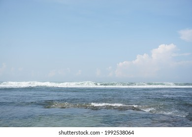 the waves are rolling towards the beach under the blue sky and cloudy sunny weather - Shutterstock ID 1992538064